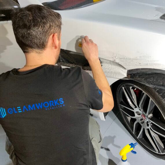 Gleamworks detailing expert installs paint protection film on a Jaguar