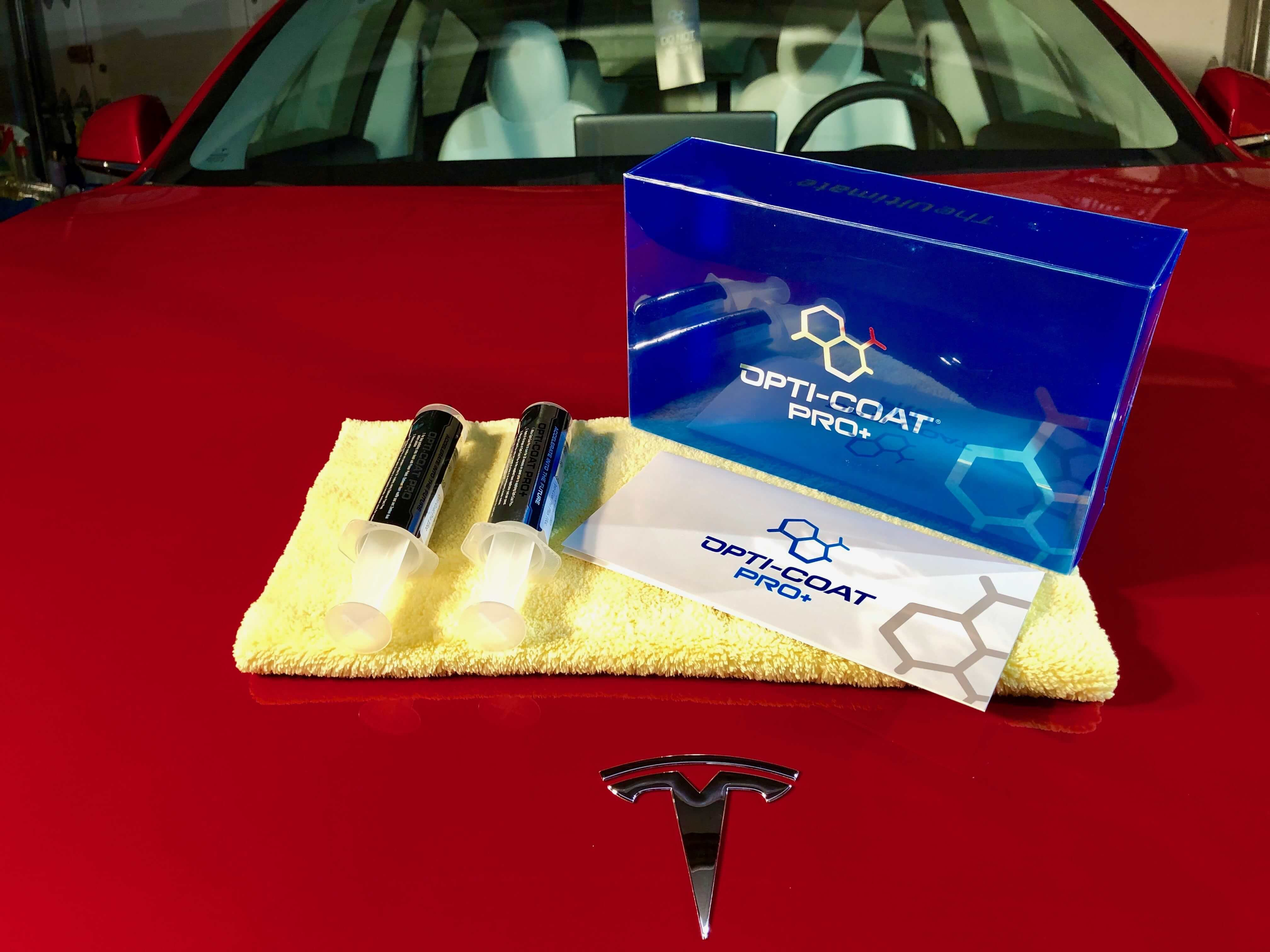 Opti Coat Pro + Ceramic Coating with microfiber towels on red tesla